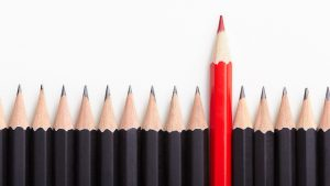 Red Pencil Standing Out From Black Pencils. Branding Tips for Businesses