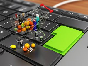 Shopping Cart Full of Grocery on a Laptop`s Keyboard