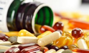 Red, yellow and white vitamin supplements pour out of a green bottle.