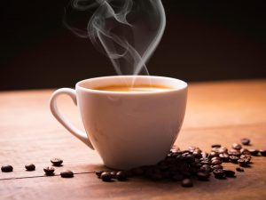 A white cup of coffee releases steam. Brown coffee beans are scattered underneath the coffee cup.