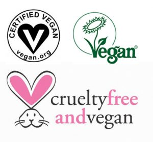 On the top left: the black and white Certified Vegan logo (A black heart with a white v). On the top right: the green Vegan Society trademark with green flower. On the bottom: PETA'S Cruelty Free and Vegan mark with a white bunny. The white bunny has pink ears.
