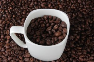 background of coffee beans and coffee beans in white cup