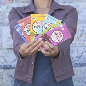 A woman holds 6 Alter Eco Foods chocolate bars.