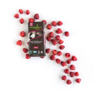 Endangered Species Dark Chocolate with Raspberries bar with grizzly bear. The bar is on top of a pile of sprinkled raspberries