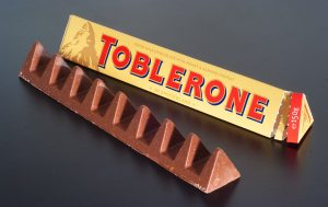 A triangular bar of Toblerone chocolate and its triangular box