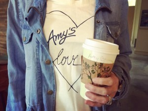 A young woman wears an Amy's logo shirt with a heart