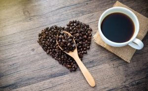 wooden spoon in coffee beans in the shape of a heart with coffee cup