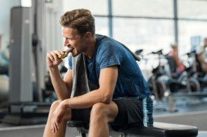 a man eating a chocolate protein bar