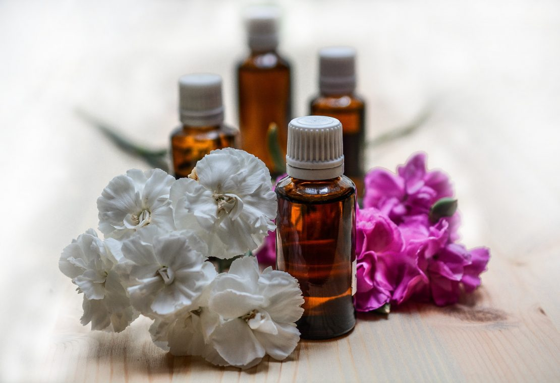 Bottles of essential oil and flowers