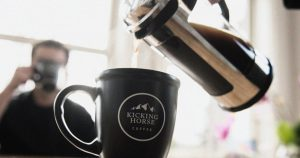 coffee being poured into a mug with Kicking Horse logo on it