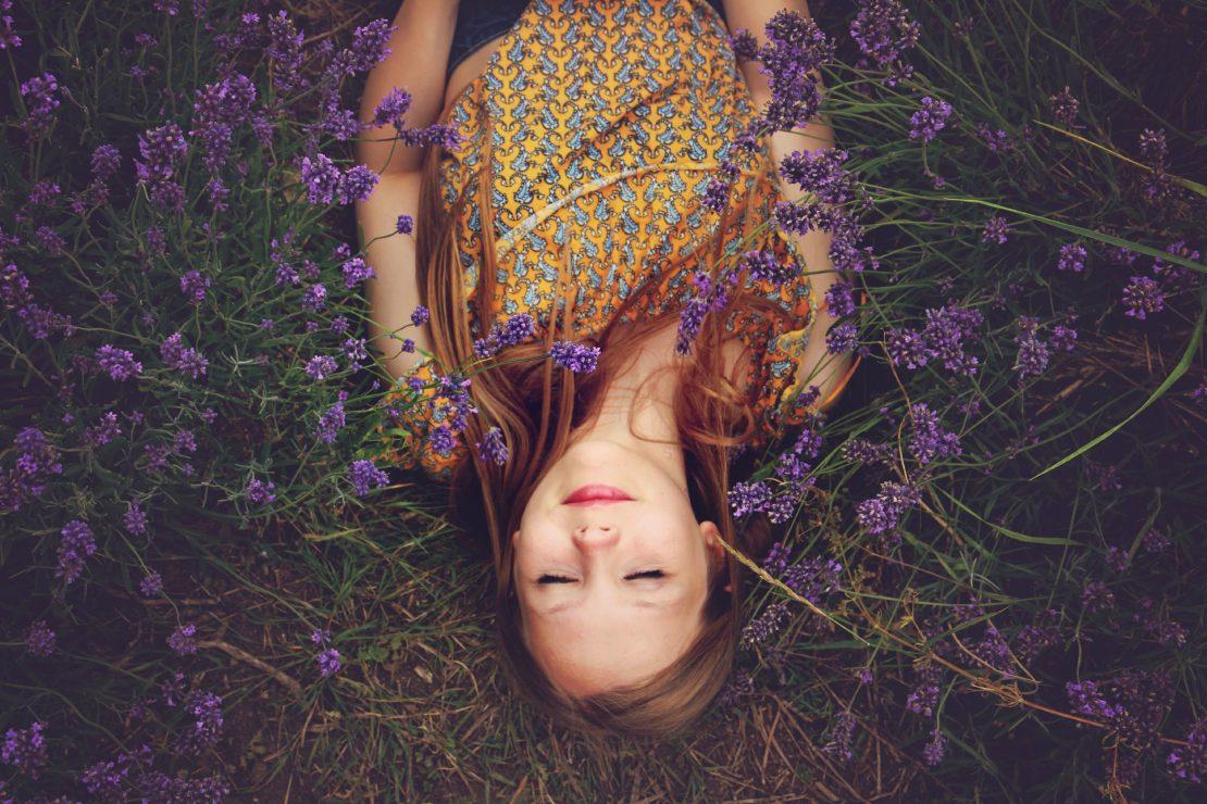 Girl lying in field of lavender flowers