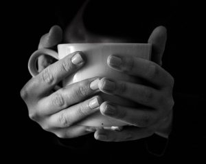 black and white hands holding teacup