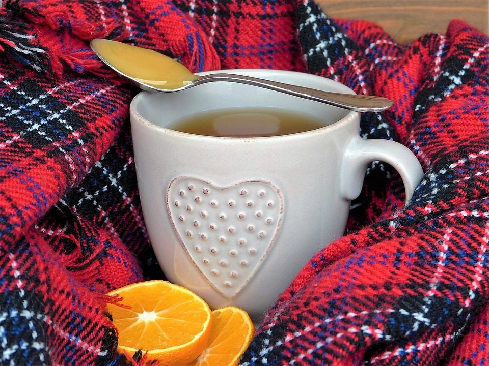 tea cup on top of a blanket with honey and orange
