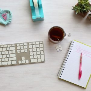 An Image Containing a keyboard, Notebook and a Cup of Coffee