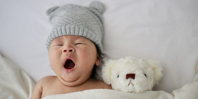 Baby yawning in bed.