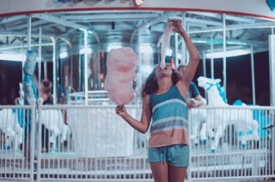 Woman eating cotton candy.