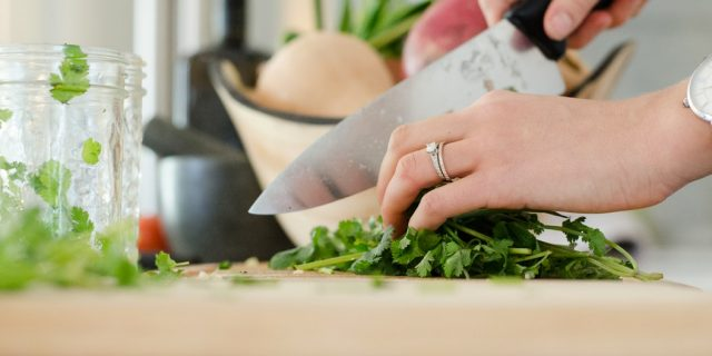 Person chopping up herbs for cooking.