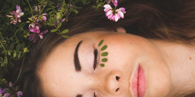 Woman with beautiful skin lying down with flowers.