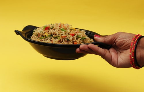Person holding a bowl of rice.
