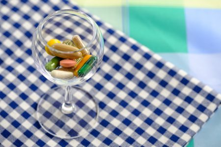 Glassful of vitamins and supplements