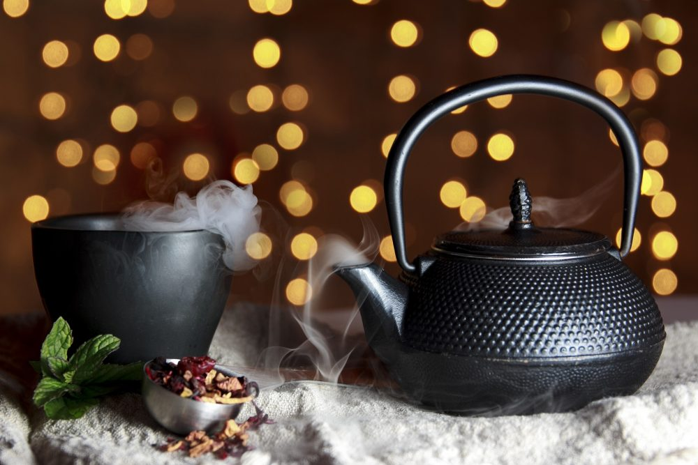 Steaming teapot and cup of organic tea
