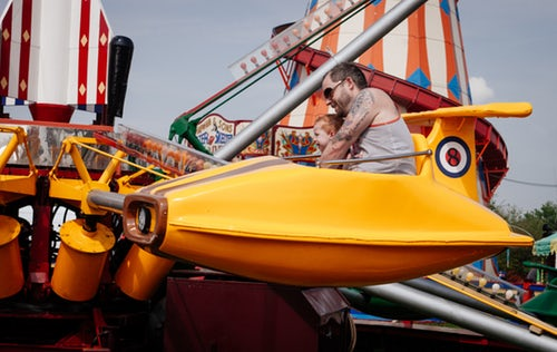 Father on amusement ride with child.