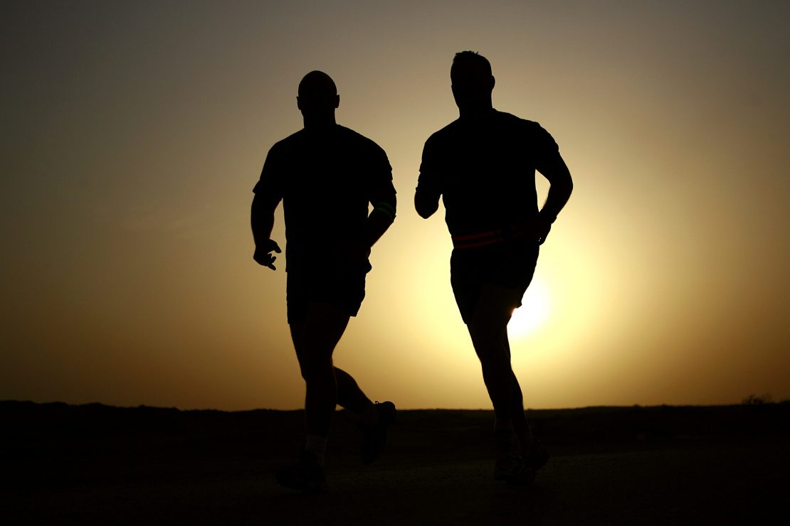Two healthy runners against sunset