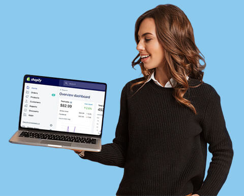Woman holding laptop showing Shopify app