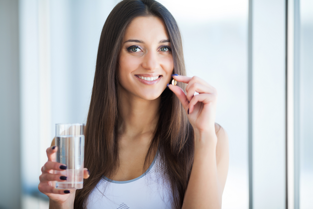 Dropship vitamins. Woman taking a daily multivitamin with a glass of water.