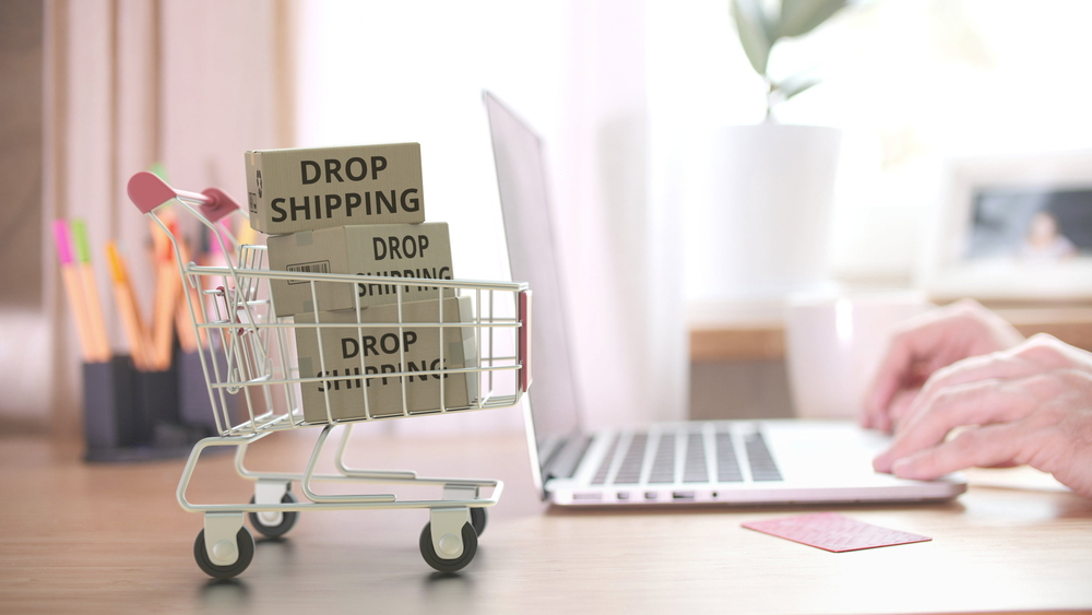 dropshipping boxes in a shopping cart next to laptop. How dropshipping food works.