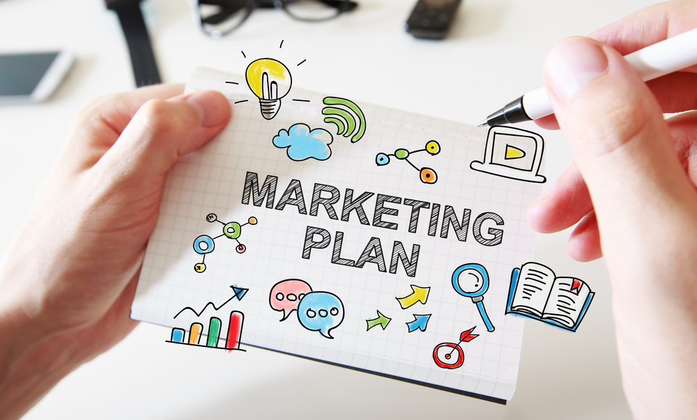 Mans hand drawing Marketing Plan concept on white notebook. Marketing organic products for dropshipping