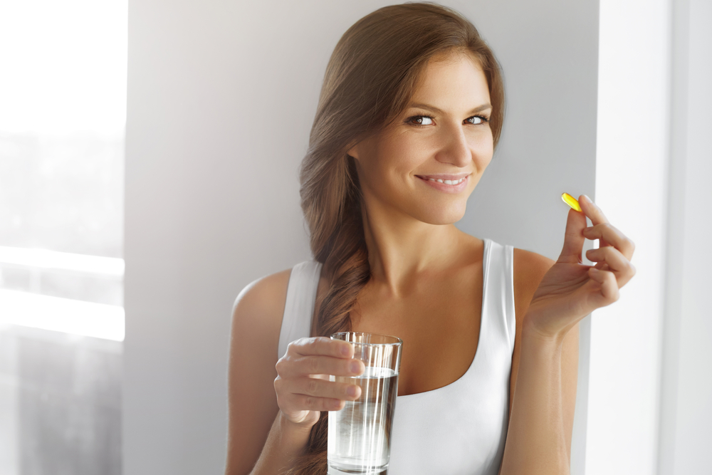 organic health and wellness products for dropshipping. Smiling woman taking a supplement.