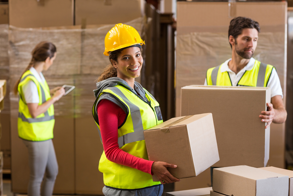 woman working in a dropshipping warehouse carrying a brown box