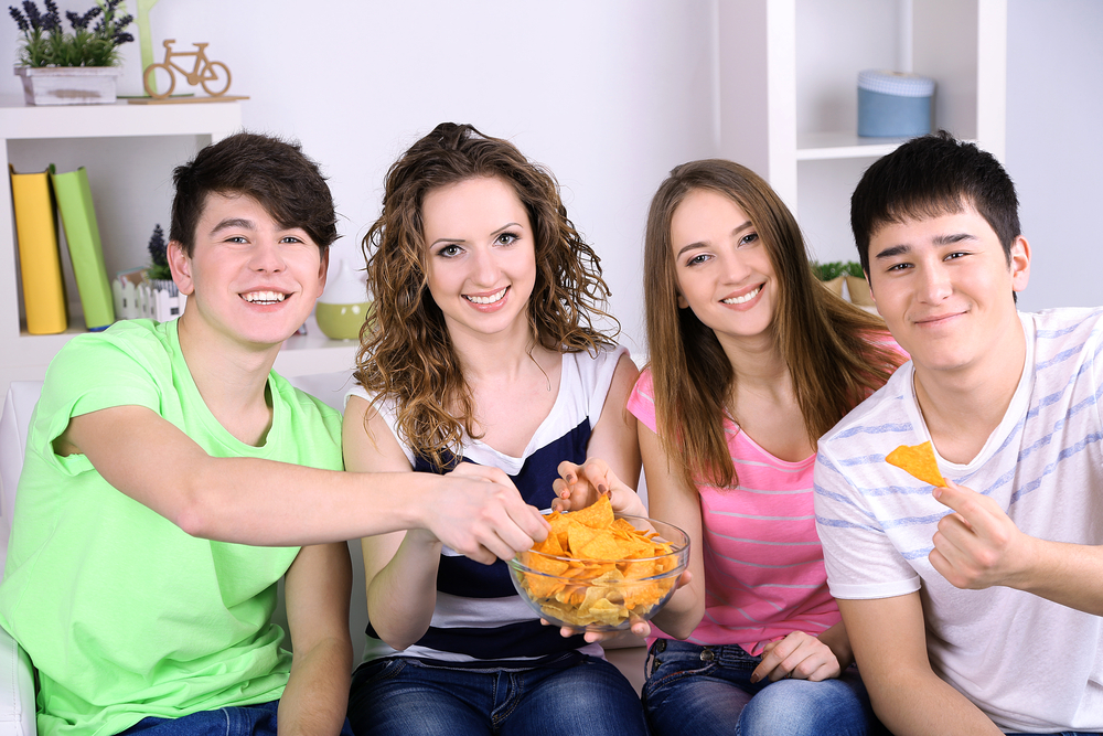 A group of friends eating snacks on a couch