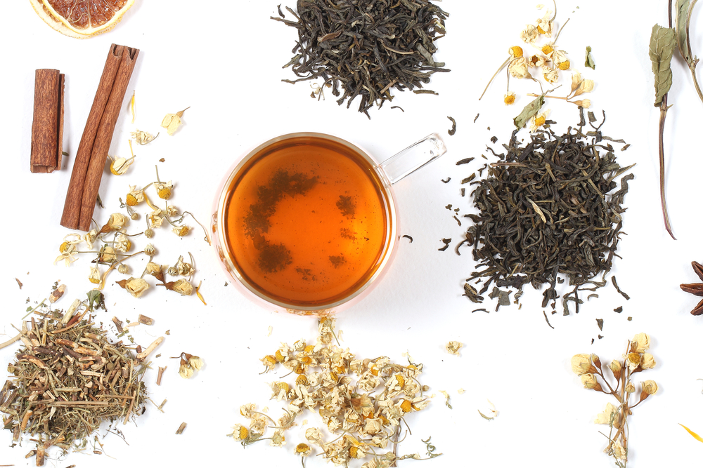 A cup of tea on a white table next to loose leaf teas