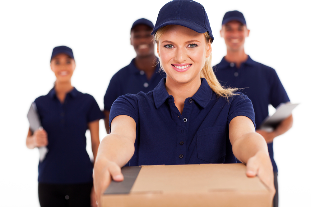 young delivery woman presenting dropshipping package with colleagues