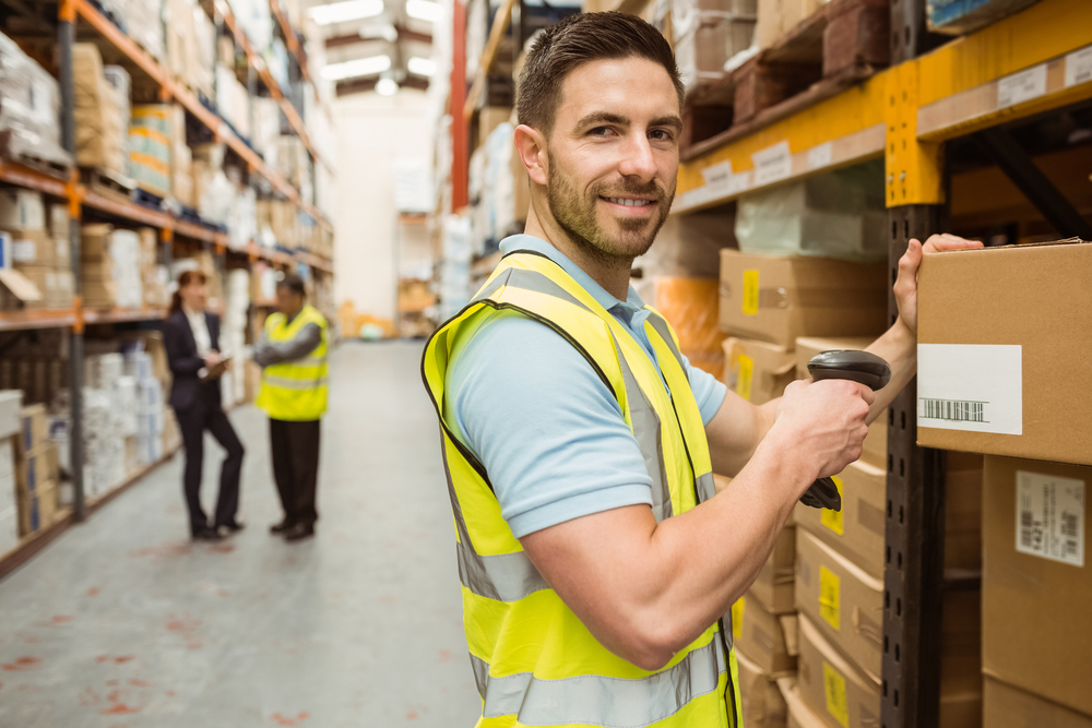 Man working in dropshipping warehouse labeling packages for shopping