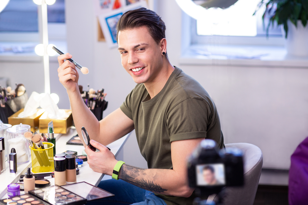 man creating a video ad for makeup showing how to use the products