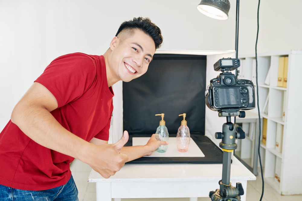 man setting up a video ad shoot with tripod and lighting