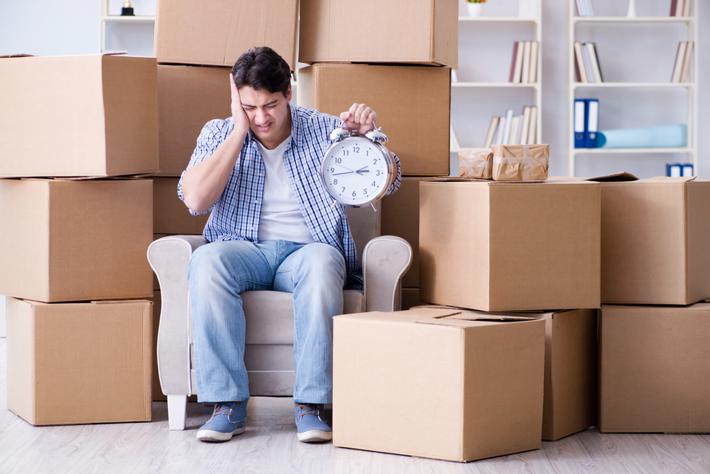 frustrated man holding a clock with packages in the background. Slow shipping times concept