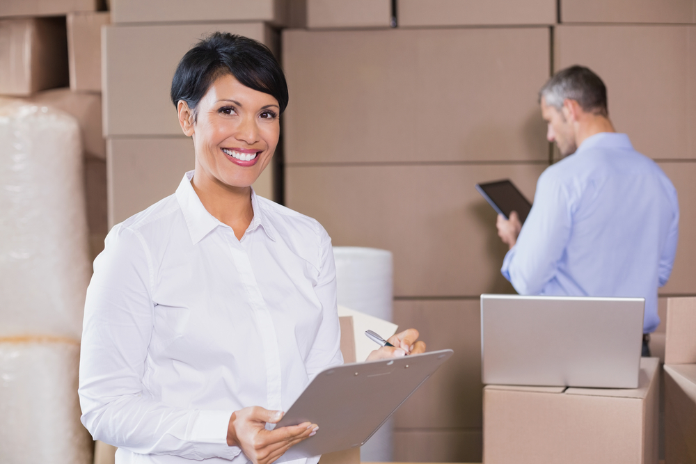 wholesale supplier smiling woman with clipboard working in a warehouse
