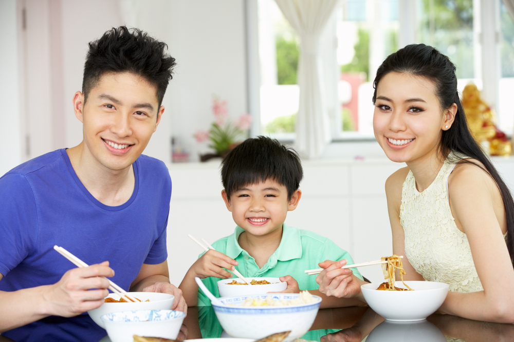 Asian family eating dinner together at the table.