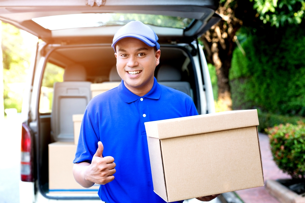 Dropshipping delivery man carrying a package and giving a thumbs up.