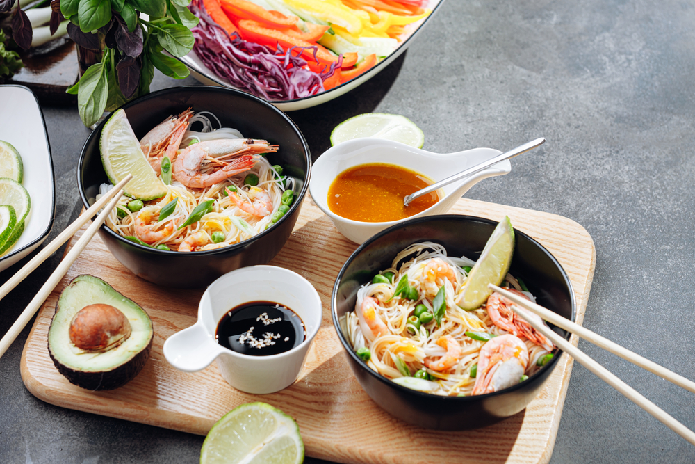Asian food being served on a wood platter